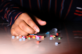 close up image of a hand surrounded by pills and drug para
