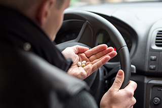 man with pills behind the wheel