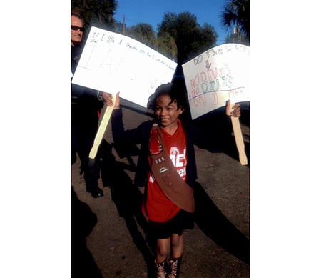 girl scout carries signs she created