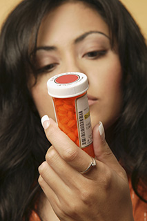 womanlookingatprescriptionbottle_article